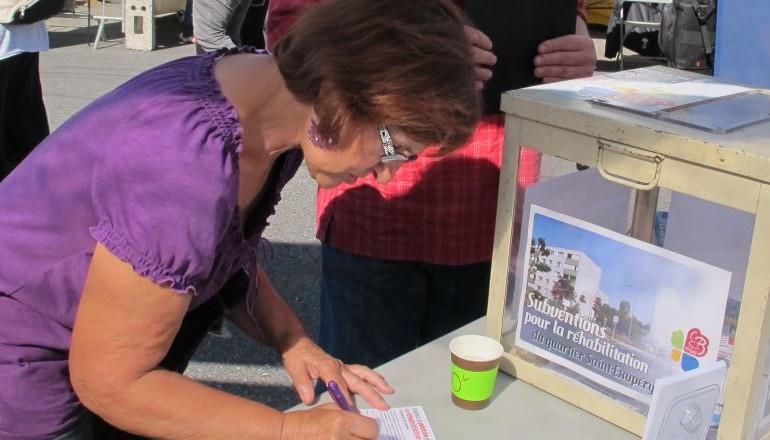 Habitante signant la pétition pour la réhabilitation de la cité Saint-Exupéry